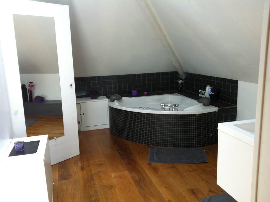 Salle de bain de la suite parentale avec lavabo, dressing et jacuzzi.