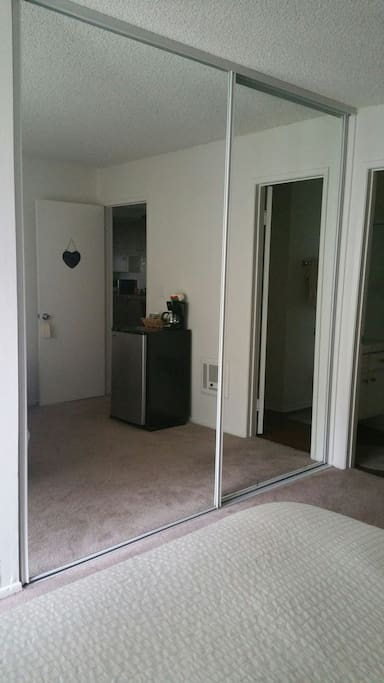 Very large mirrored closet with wooden hangers inside.
