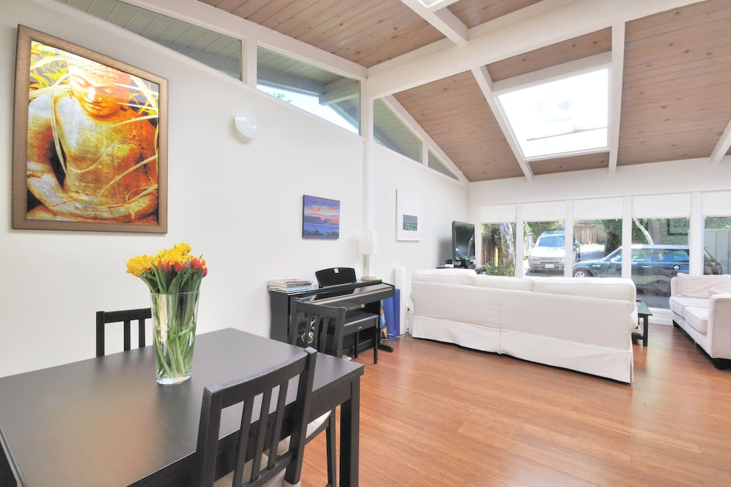 Enjoy the natural light and spacious feeling in the open floor plan, showing the dining room and living room.