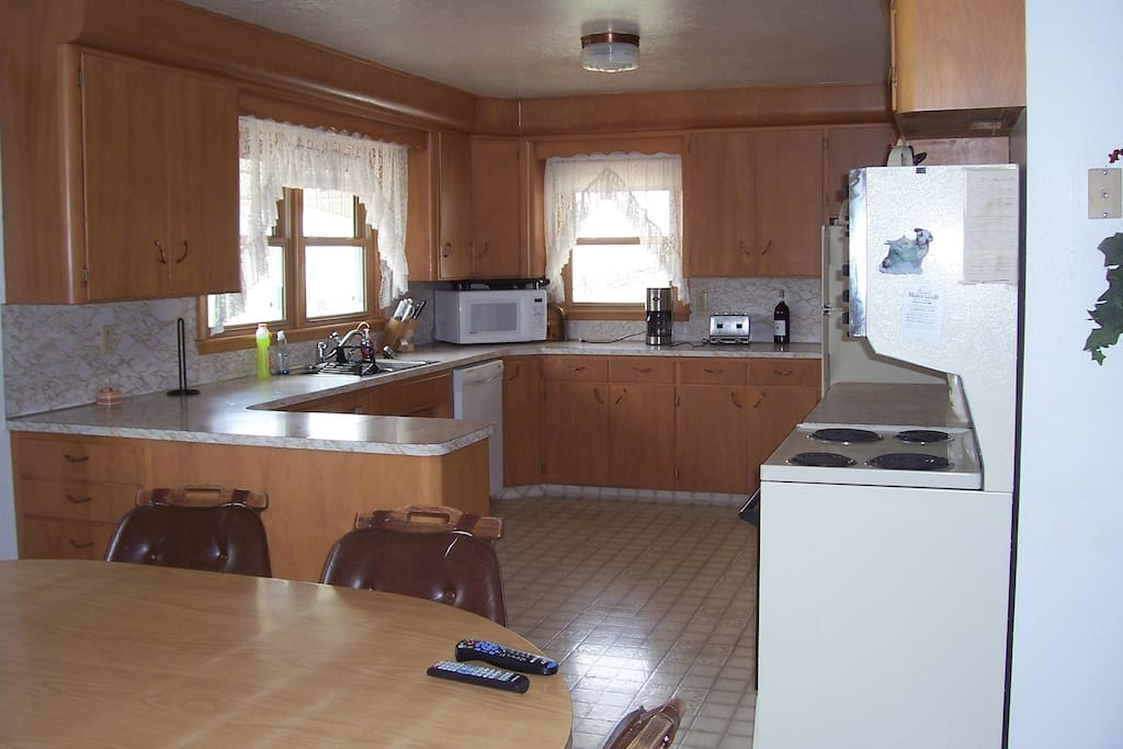 Large country kitchen is fully furnished with dishes and cook ware.