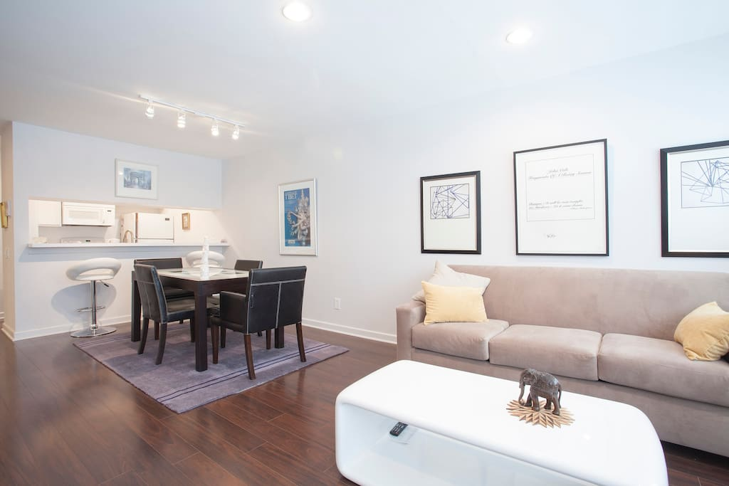 Get an overall idea of what part of the 720 sq.ft. space looks like as you enter the apartment. You can see how the living room area blends into a sophisticated dining section with a bar and look-through to kitchen.