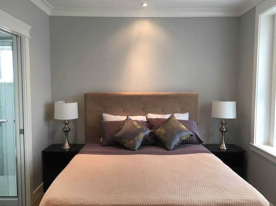 Well-lit Guest bedroom with a number of lighting options and a private bathroom.