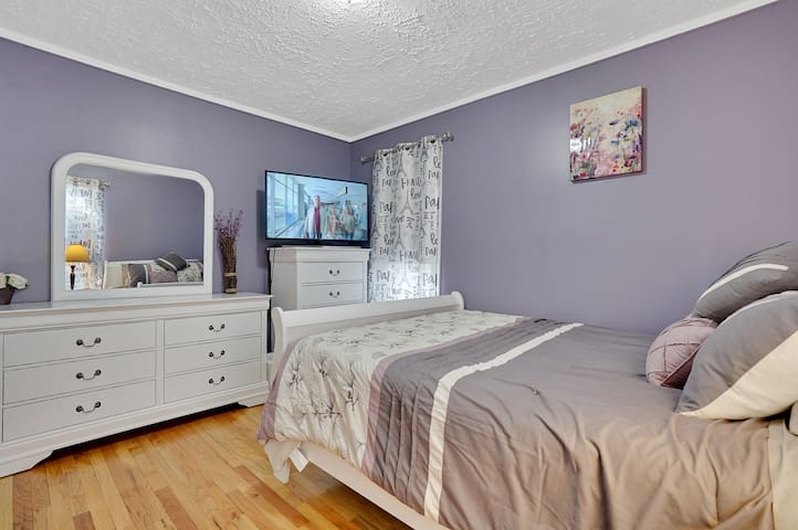 Spacious downstairs cute bedroom with new queen sized bed, night stand, table lamp, new cute  comforter, additional comfy thin quilt, new big LED Samsung TV, closet, new chest, new dresser with mirror and fan