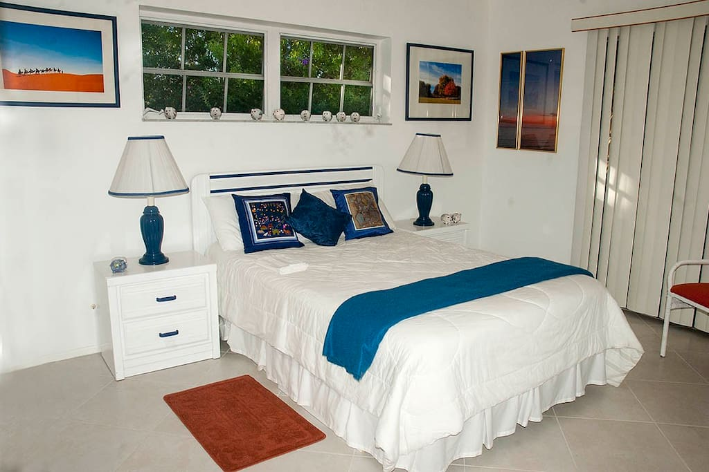 The available bedroom is crisply decorated in white and royal with splashes of orange