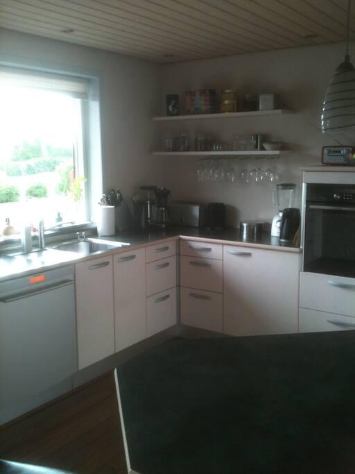 Funktionel køkken, hvor skabe og skuffer er fyldte. køleskabsplads til rådighed.