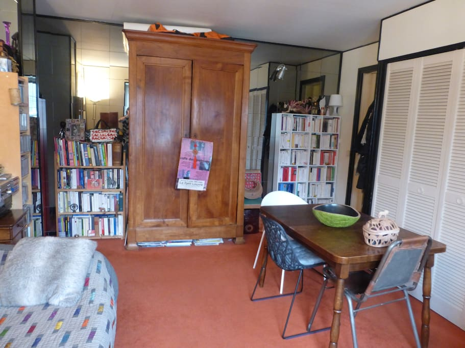 Séjour/salle à manger avec de nombreux livres et une télévision