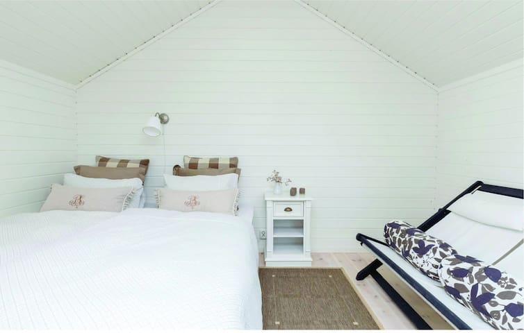Guest house with queen size bed and seating area.