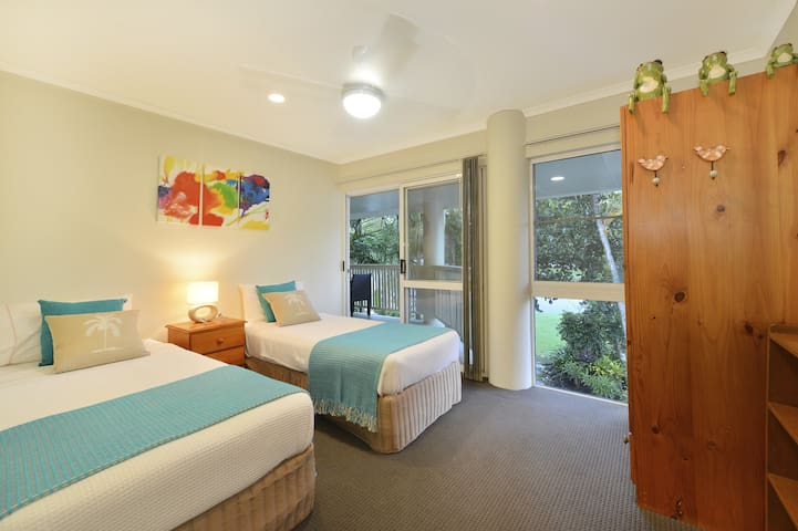 second bedroom upstairs with two single beds facing the tropical lush gardens upstairs