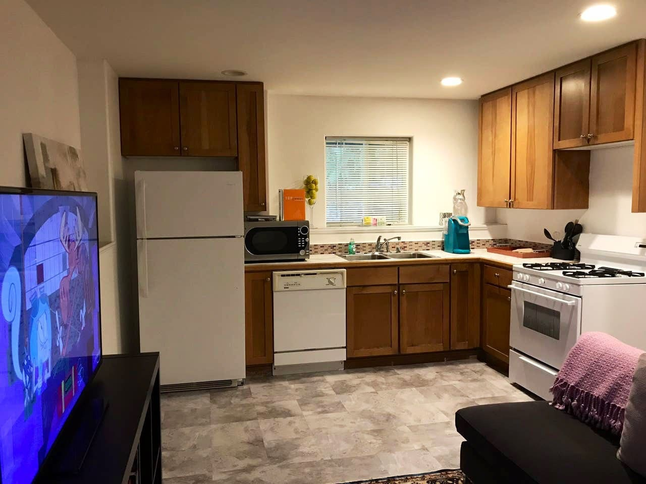 Living Space with flat screen TV connected to a Full Kitchen