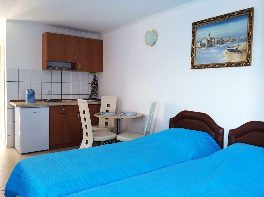 Кухонный гарнитур с варочной панелью, холодильником, раковиной, чайником и набором посуды, необходимой для приготовления еды.
