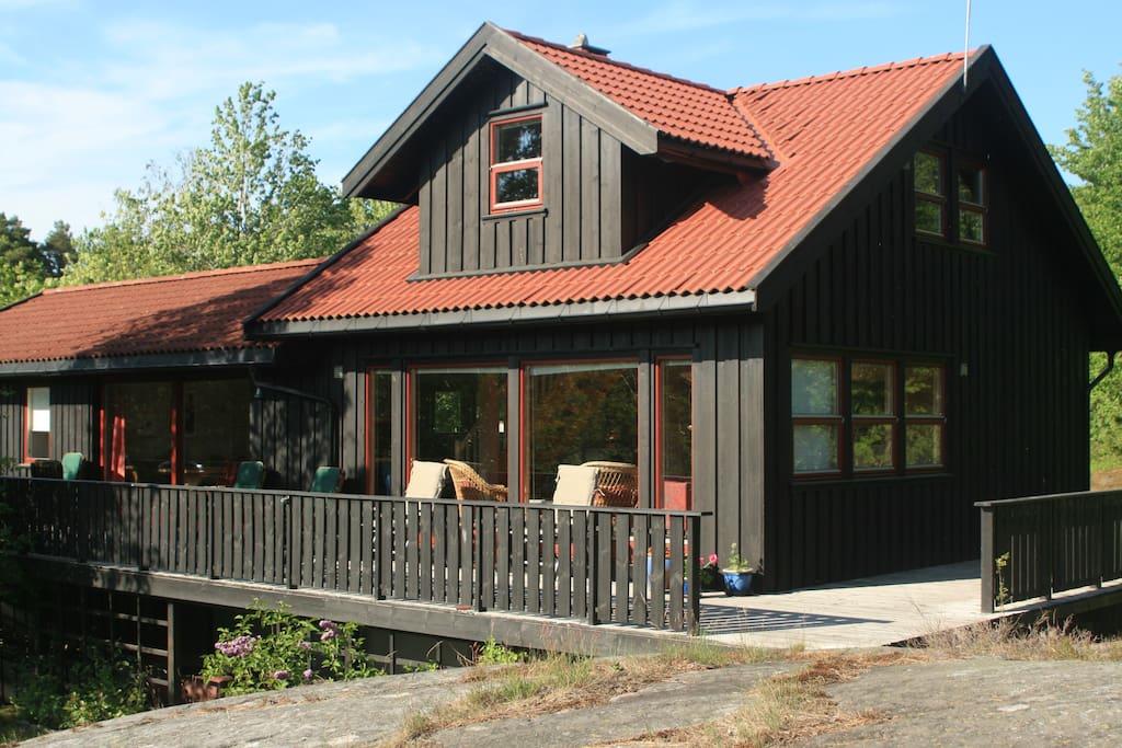 Flott terrasse rundt hytta med utemøbler og grill.