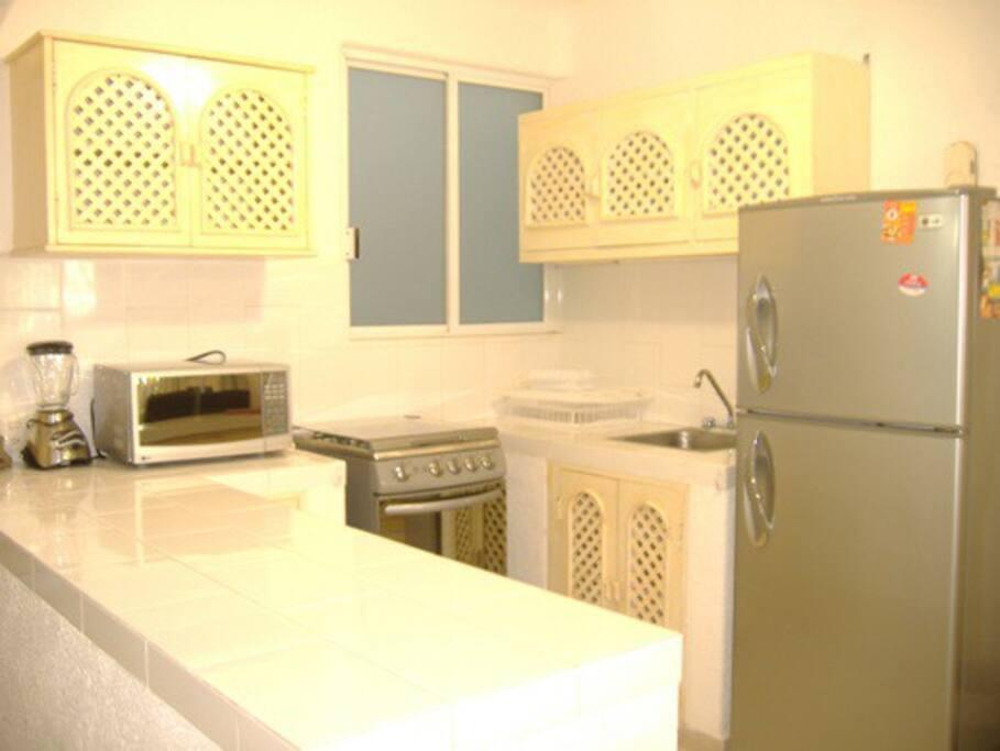 Una espaciosa cocina con aparatos y utensilios nuevos.