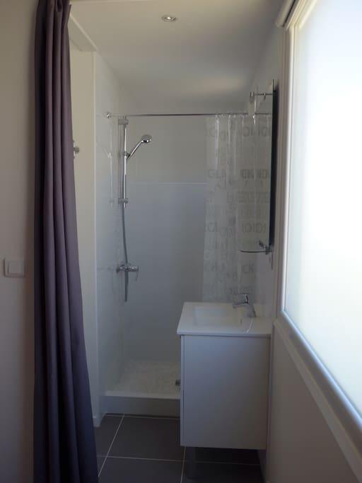 Salle d'eau avec toilettes (sur la gauche), séparée de la chambre par un rideau.