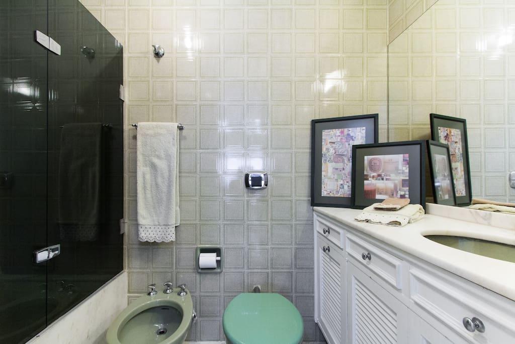 Banheiro da suite com bancada e piso de marmore, box em blindex, roupa de banho para duas pessoas de qualidade.