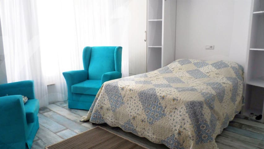 A comfortable double bed. There is one turquoise chair at the moment to create more space.