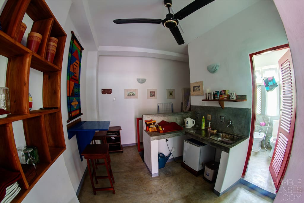 small kitchnette, with fridge, sink, table & 2 stool