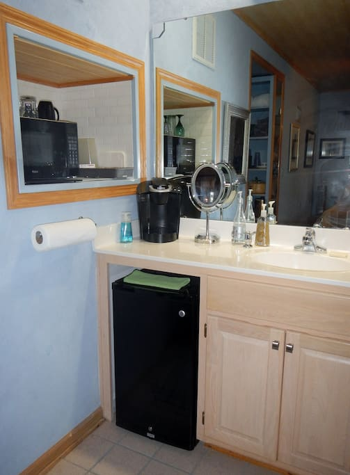 The vanity area equipped with fridge, microwave, and coffeemaker.