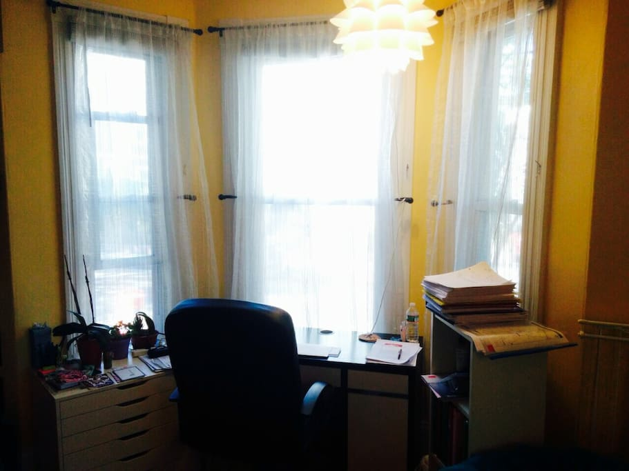 A desk with plenty of light and a view of the street sits in a bay window in the bedroom.