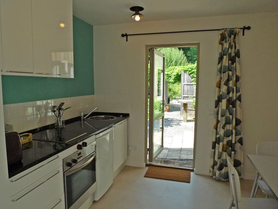 Kitchen/diner with Lucienne Day print curtains looking out to courtyard garden