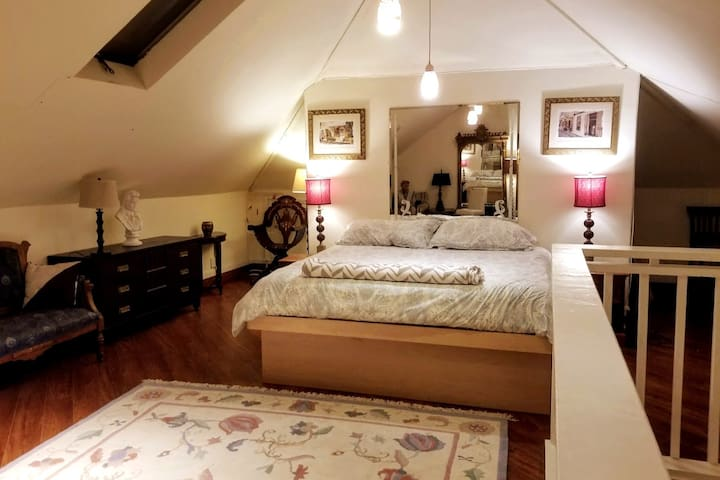 King-size bed / sleeping area occupies one end of the upper floor