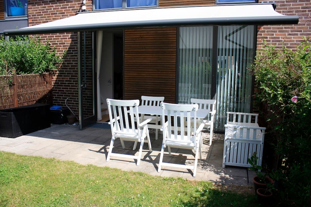 Terrace in the small backyard with access to the communal green areas and playgrounds.