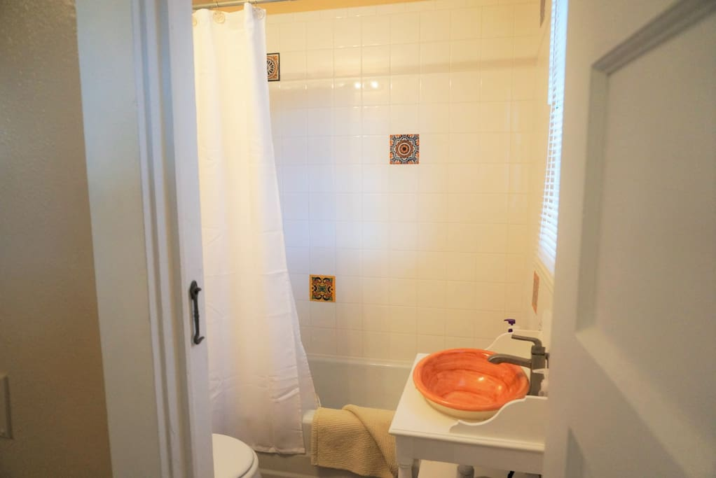Private attached bathroom with shower over tub.  New tiling, flooring and vanity.