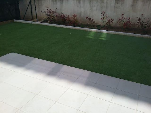 Petit espace vert recouvert d'une pelouse synthétique