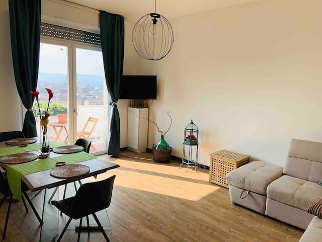 Salotto/sala da pranzo con divano letto matrimoniale, TV, e un terrazzino e vista sulla città.  Living room with double sofa bed, TV,  and small terrace overlooking the city.