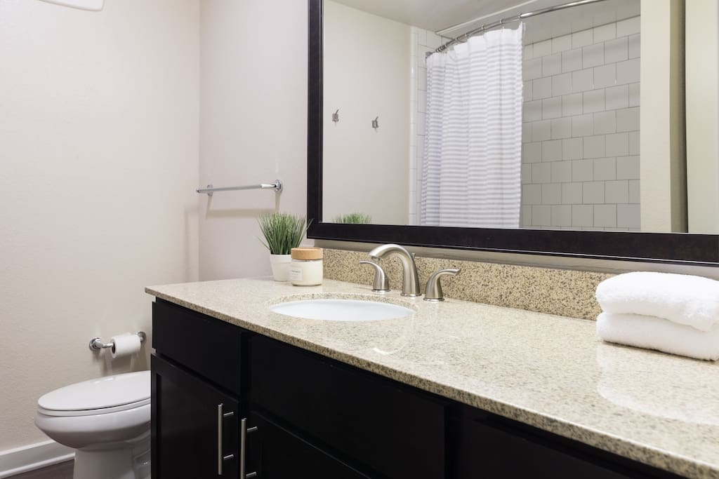 Huge bathroom with a spacious vanity, hairdryer, bath amenities and more.