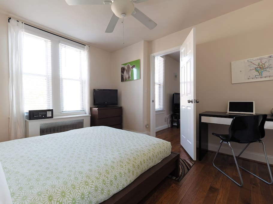 Queen size bed in large bedroom. TV, hotel safe, and workspace.