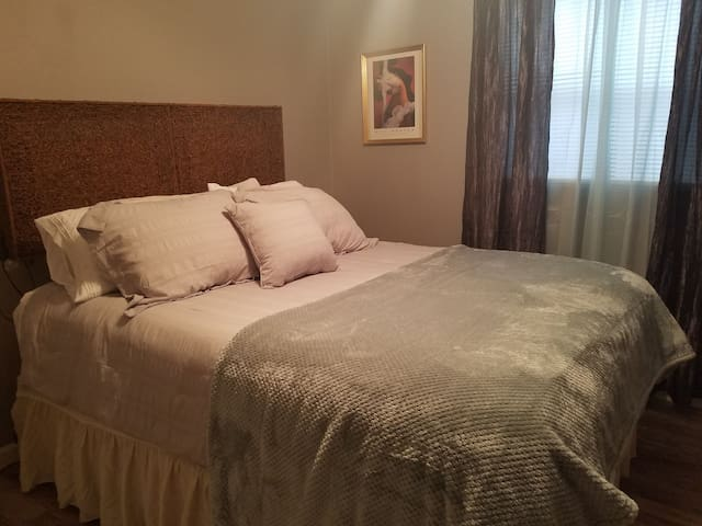 Queen size bed with soft bedding.