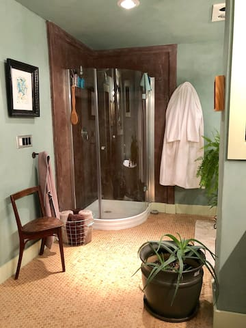 The stand-up corner shower features tadelakt walls and a rainfall shower head. There are fresh linens and fluffy bathrobes to use during your stay.