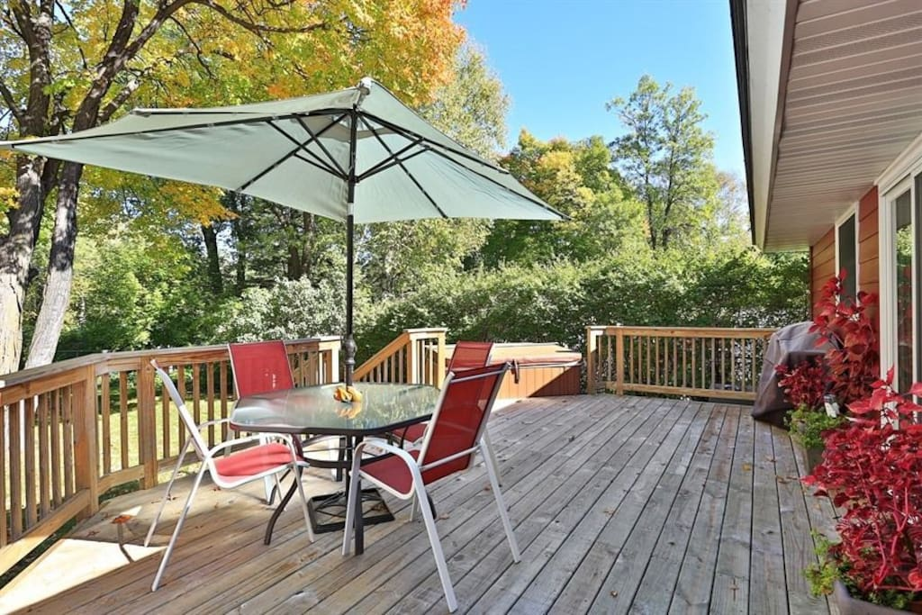 Outside deck with hot tub with a sliding glass door into the house