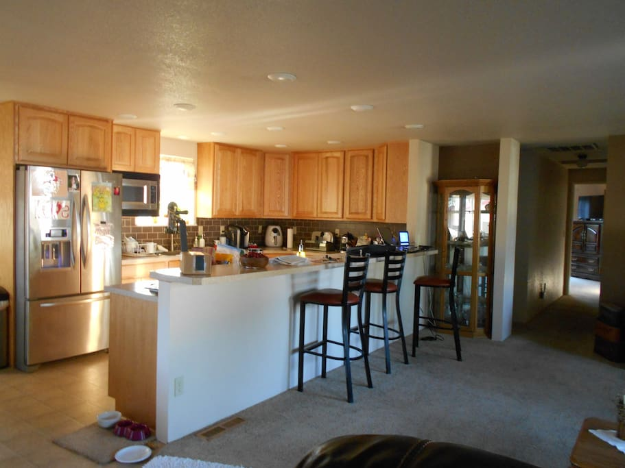 Open kitchen with par sitting and view into living area.