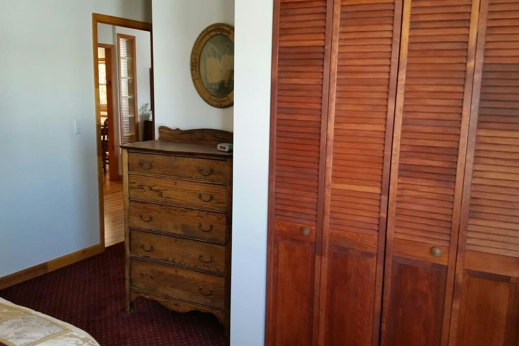 Closet and dresser in bedroom.