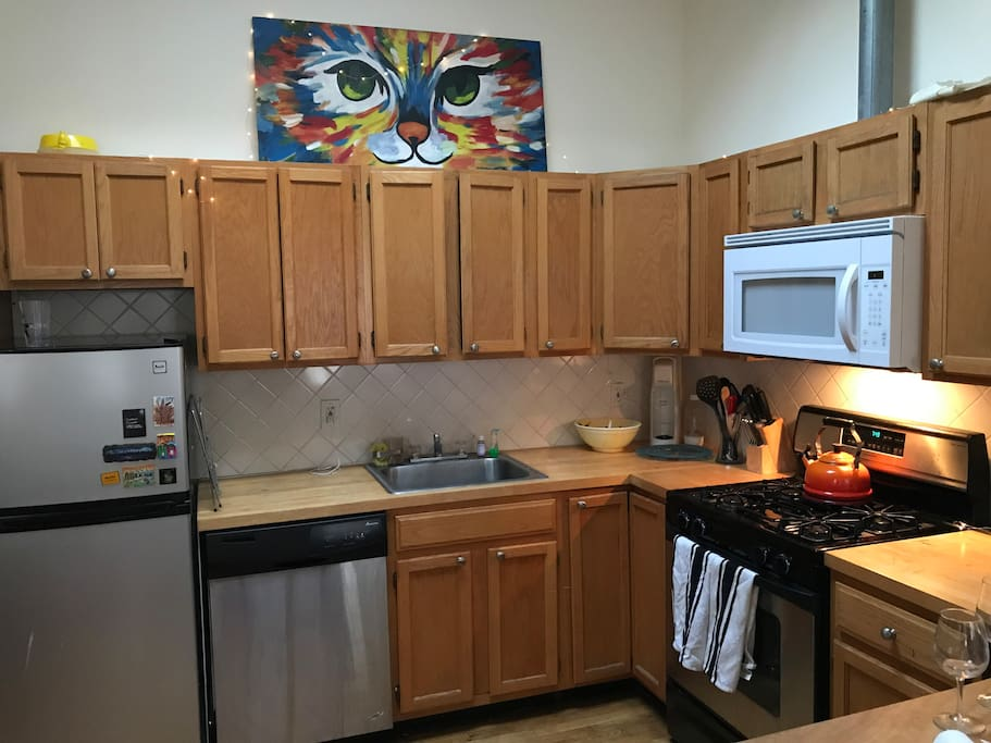 The kitchen is huge for New York and part of the open concept living space. It's fully stocked with gas over range, a French press, tea kettle, wine glasses galore, a dishwasher and fridge.