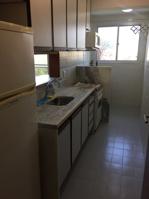 Cozinha com geladeira, fogão e microondas