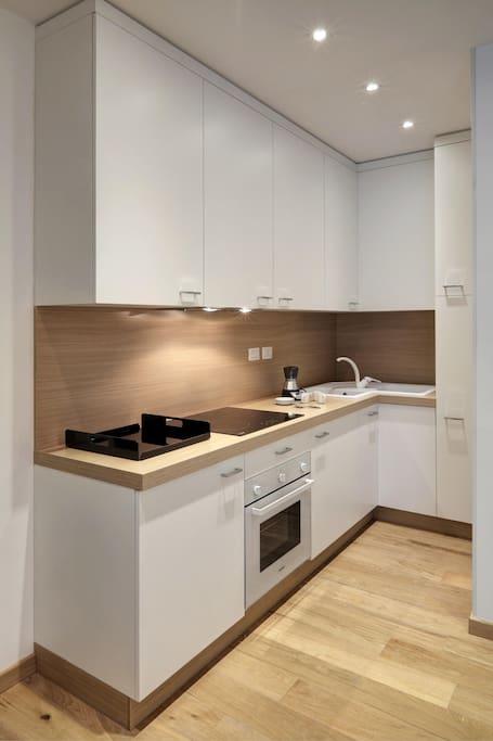 cucina attrezzata con frigo, forno, stoviglie, macchina da caffè e lavasciuga