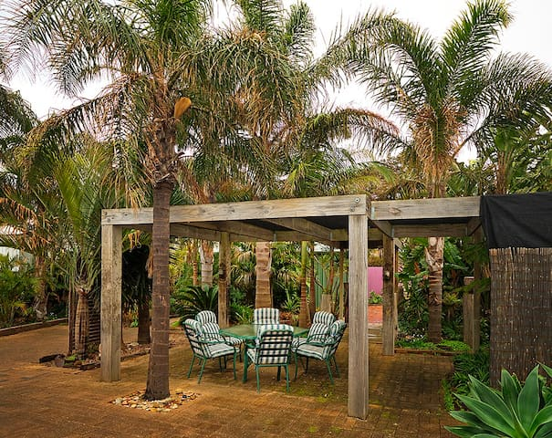 Quiet outdoor dining area with barbeque set amongst  a beautiful palmed garden