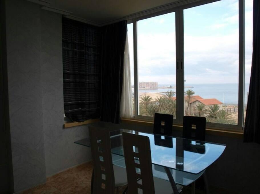 Обеденный стол возле окна с видом на море в общей комнаты