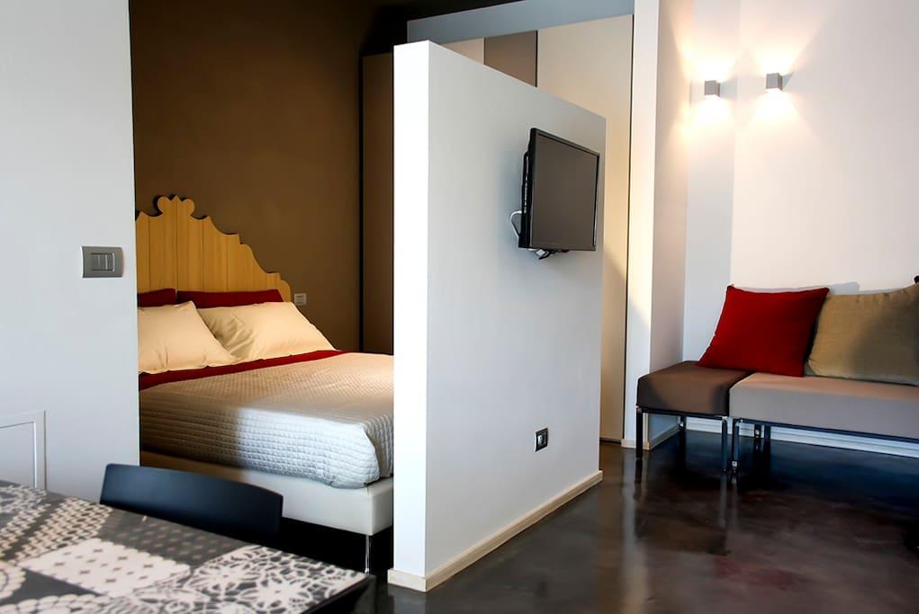 open space con letto matrimoniale e divano letto