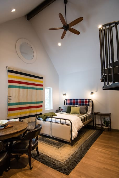 "The ""Haw"" side has a queen size bed on the main level, next to the ""Haw"" side bathroom. A spiral stair leads from this space to a semi-private loft."