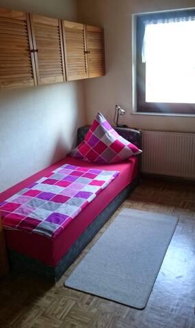 Schlafzimmer mit Einzelbett und klappbarem Gästebett