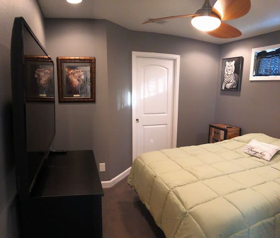 bedroom with queen sized bed, walk in closet, TV, night stand, and dresser.