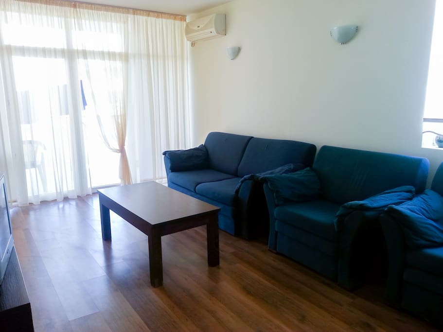 Living room:  a view outside the terrace window. Living room has a double sofa bad and two armchairs.