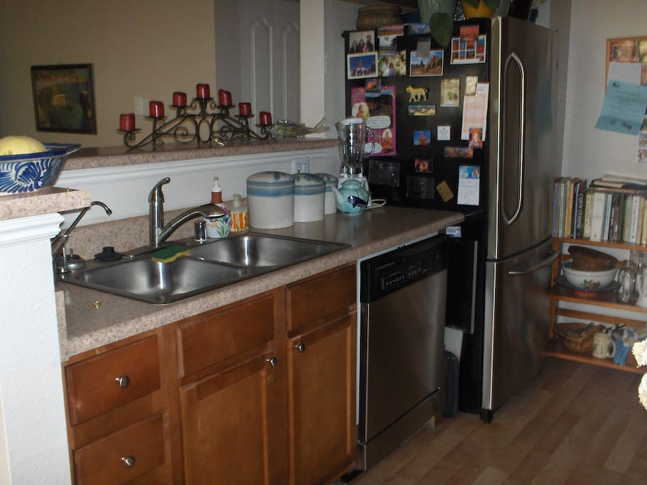 Galley kitchen open to living and dining room with new appliances.