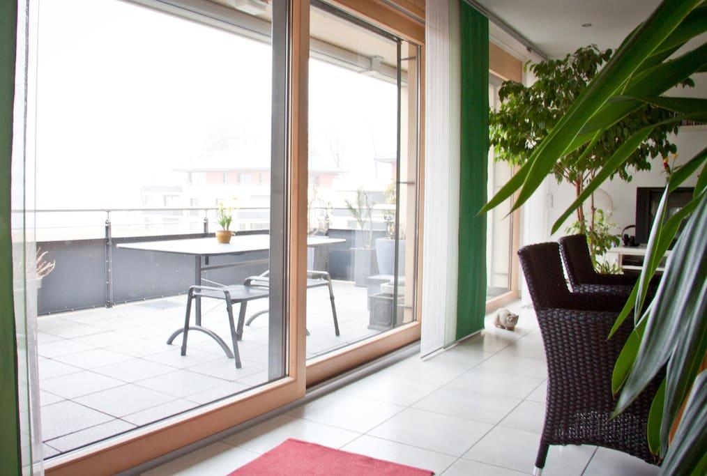 Großer Balkon mit Sonnenmarkise - die Stühle sind noch eingewintert