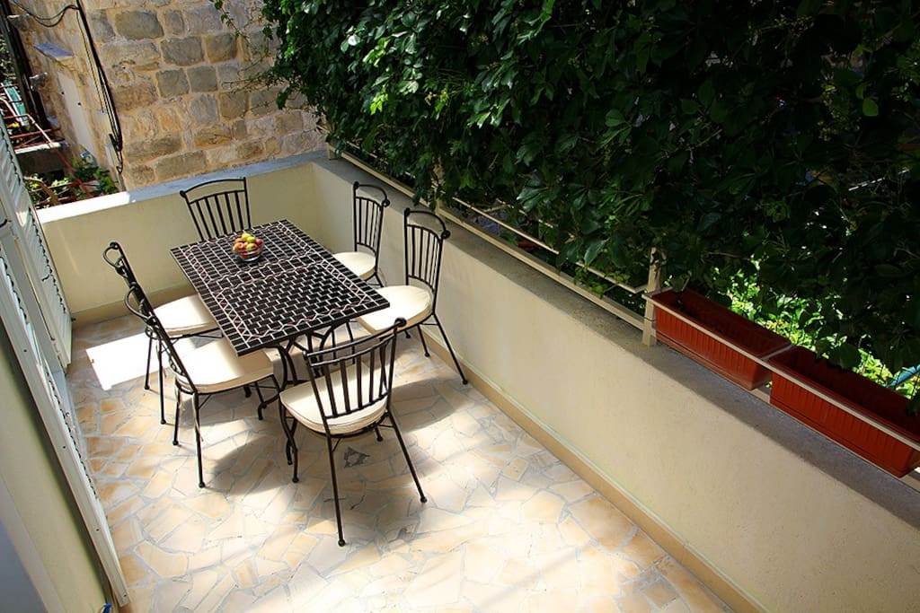 Shaded terrace with table for 6 in front of dinning room