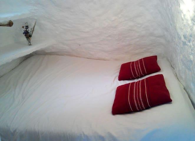 Espacio excavado con cama de matrimonio