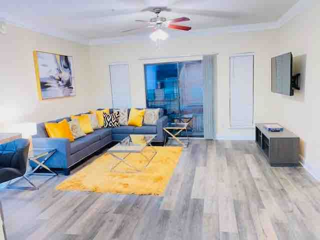 Upscale living room (daytime view) with sectional style seating. This room is capable of seating 5-6 people. The room also comes equipped with glass end tables, high speed Wi-Fi, and a 55 inch 4k ultra HD smart TV